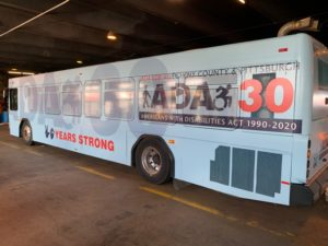 "Photo of side of Port Authority bus wrapped in blue with ADA 30 logo and text that reads ""30 years strong"""