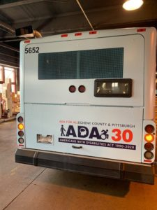 Photo of back of Port Authority bus wrapped in blue with the ADA 30 logo