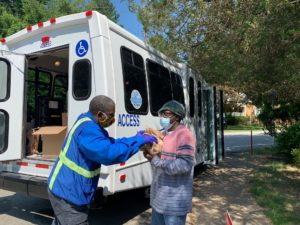 Image of ACCESS driver handing woman meals