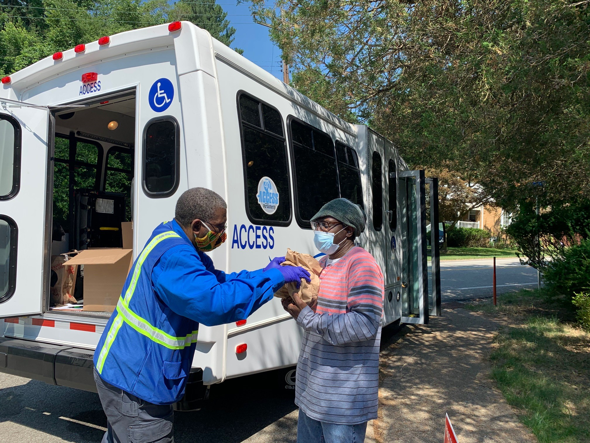 Image of ACCESS driver handing meals to woman in front of white ACCESS van